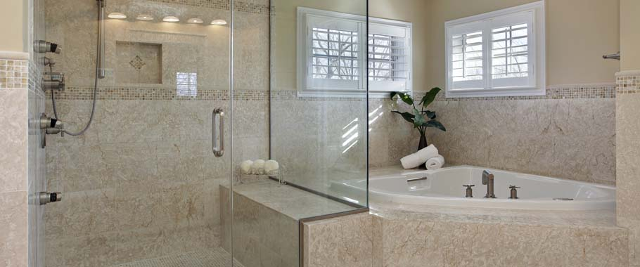 Glass shower enclosure in granite bathroom